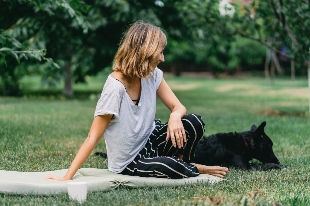 Dog and woman sitting on grass.