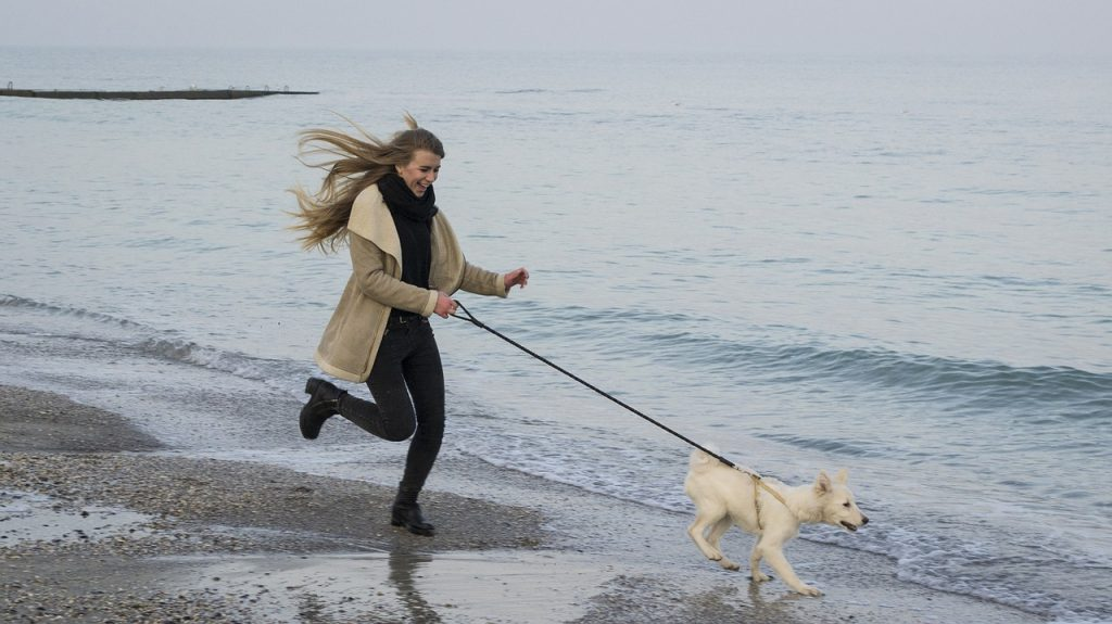 Woman running with dog by beach.