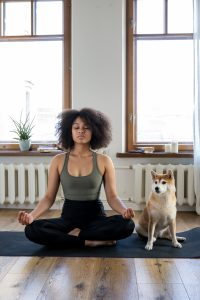 Woman doing yoga beside her dog.