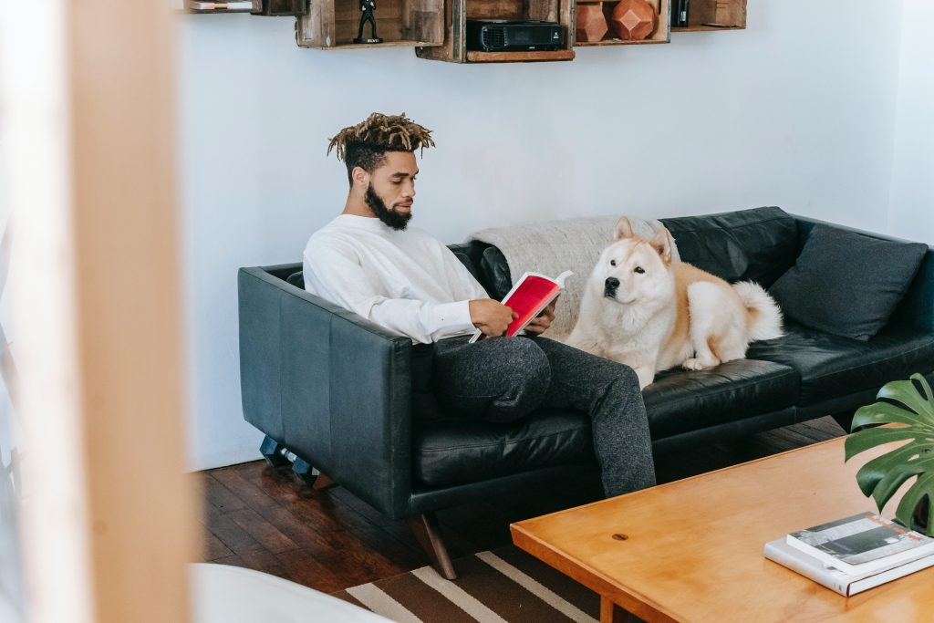 Dog sitting beside man on couch.