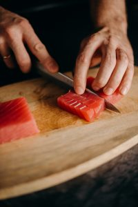 A person slicing tuna for sushi.