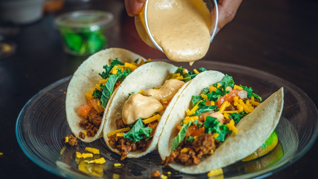 Pouring sauce over tacos.