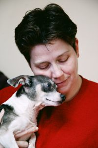 Woman in red shirts hugging a dog.