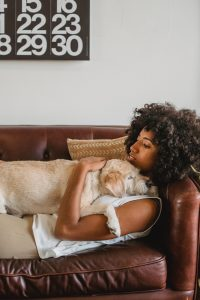Woman and dog lying on the couch.