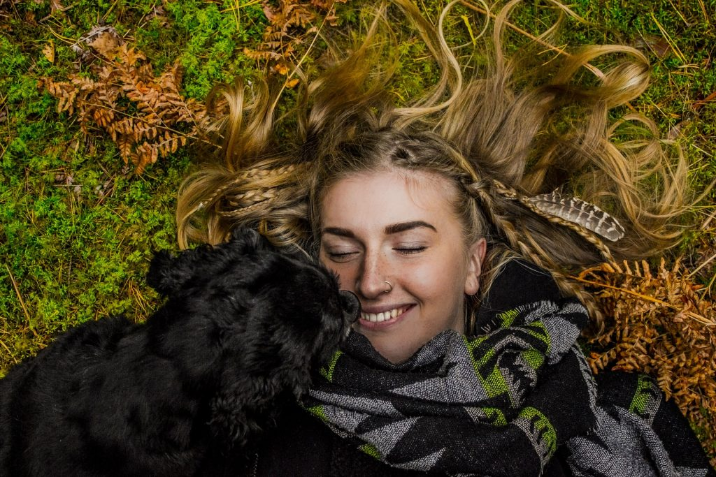 Woman and black dog lying on grass.