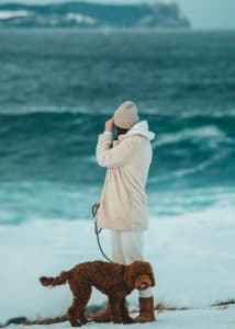 Woman on beach with Labradoodle.