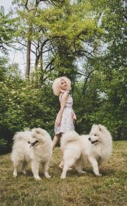 Woman with curly hair and two dogs.