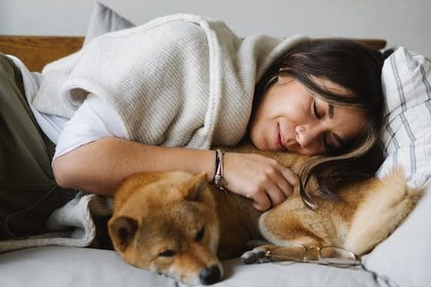 Woman snuggling with dog.