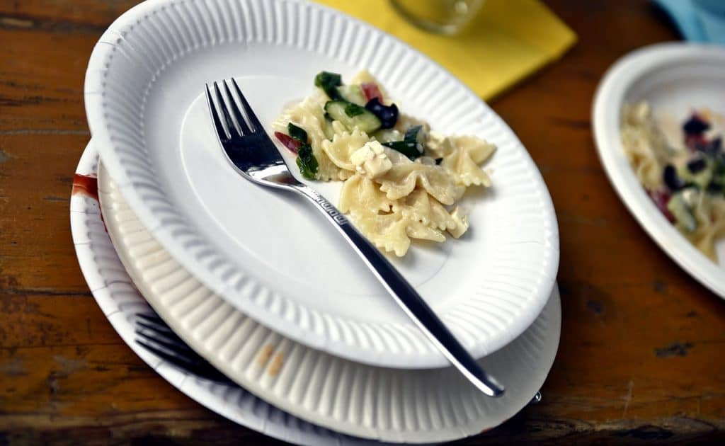 Paper plate with fork and pasta.