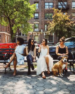 Women on bench with a dog.