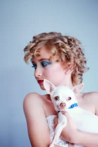 Woman posing with chihuahua.